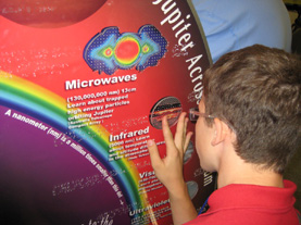 A visitor examines the SSREK tactile graphics